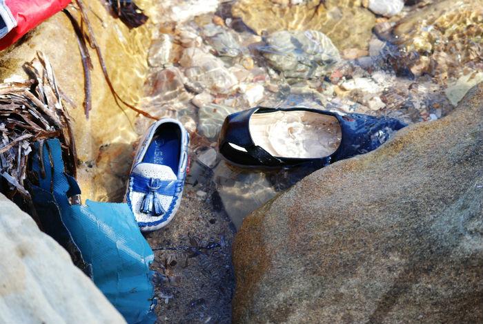 Zapatos perdidos de niños que llegan a la costa griega escapando de la guerra